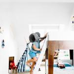 Stockbett in weißem Kinderzimmer, Junge auf Bettleiter